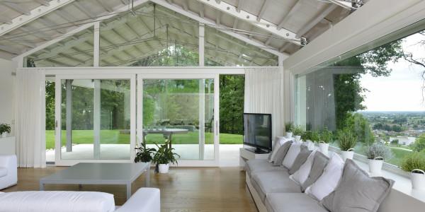 Porta alzante scorrevole e finestre sagomate ad alte prestazioni termoacustiche. Finestrone lunghezza 6,5 mt. con apertura a bilico.