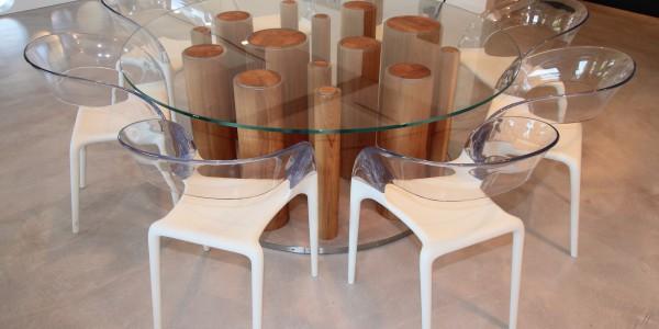 Tavolo con base in resina e acciaio con colonne in legno di rovere massiccio e piano di cristallo extrachiaro.