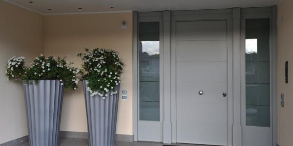 Portoncino blindato con parti laterali fisse a vetro e colonne esterne in rilievo